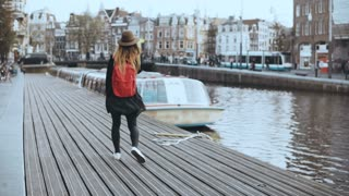 Cute tourist female walks, talks on the phone. Happy relaxed traveler walking along river boat embankment. 4K back view.
