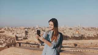 Cute tourist girl talks on video call. Jerusalem Israel. Pretty European traveler woman smiling happy and excited. 4K.