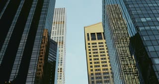 Day to night 4K timelapse of New York buildings. Tall highrise skyscrapers low angle POV shot. Sunset and twilight.