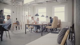 Dolly shot of casual multiethnic millennial people enjoying working together in healthy workplace office atmosphere 4K.