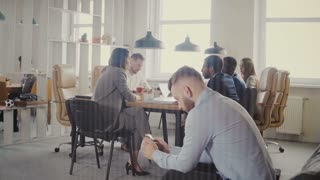 Dolly shot of multiethnic business meeting in modern office. Young successful European businessman using smartphone 4K.