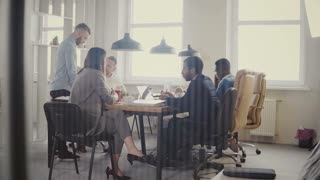 Dolly shot of teamwork at loft modern office table. Multiethnic business people cooperate, discuss market at meeting 4K.