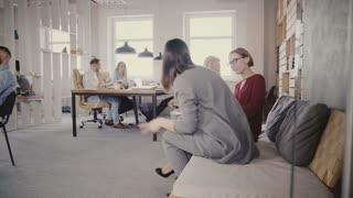 Dolly shot of two female colleagues get up from office couch, walk away in modern office. View through glass wall 4K.