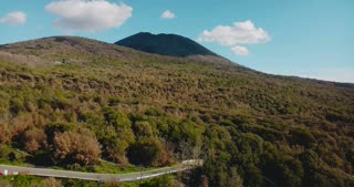 Drone ascending above Vesuvius volcano, Italy. Aerial view panorama of amazing summer mountain forest and clear sky. 4K.