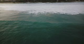 Drone camera follows huge blue ocean foamy wave rushing to beautiful exotic resort shore with tropical trees and houses.