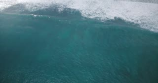 Drone descending and zooming in on sea water surface and giant mint blue rushing sea wave crashing down with foam.