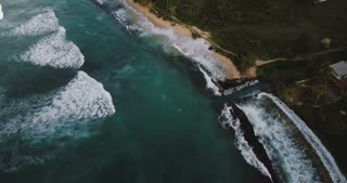 Drone flying above beautiful foaming sea waves reaching ocean coast line with tropical trees, houses, hotels and boats.