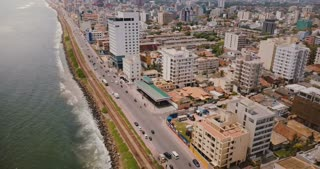 Drone flying above Colombo coast, Sri Lanka. Amazing aerial view of city street traffic, modern buildings and ocean.