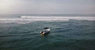 Drone flying above small boat and ocean waves, turning back to reveal magnificent tropical resort house on the shore.