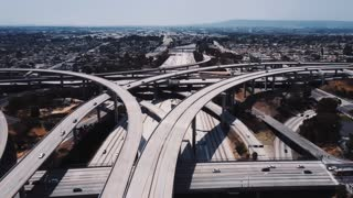 Drone flying around Judge Pregerson highway junction in Los Angeles, cars going over complex flyovers and intersections.