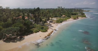 Drone flying around small idyllic ocean resort house with palm trees, waves washing the shore with clear blue water.