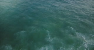 Drone flying backwards behind an ocean wave over amazing natural seafoam texture of blue and mint green rising up.