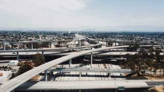 Drone flying backwards over large highway interchange in Los Angeles, USA with traffic moving through many road levels.