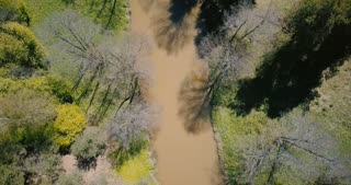 Drone flying close above early spring muddy river. Aerial 4K vertical view beautiful warm sunny springtime wilderness.
