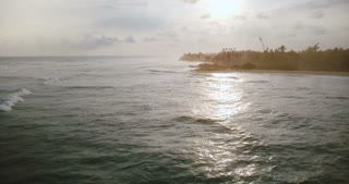 Drone flying forward along incredible exotic tropical sunrise beach, waves reaching coast line and crashing with foam.