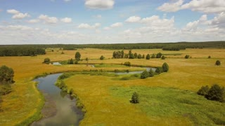 Drone flying forward over meandering river. Aerial shot of beautiful European rural landscape. Bright summer field 4K.