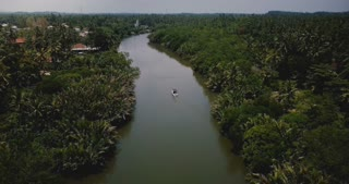 Drone flying forward over small boat on beautiful wide river flowing in the jungle wilderness among tropical green trees