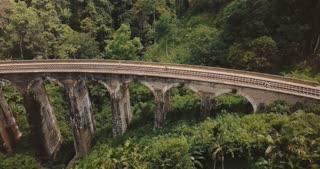 Drone flying left opening beautiful panoramic view of Nine Arch Bridge Ella in Sri Lanka, historic architecture landmark
