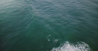 Drone flying low over high foaming waves in open ocean. Peaceful vertical view of blue tides breaking over sea water.
