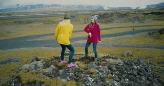 Drone flying near the two woman on the top if the mountain and dancing together. Tourists in the lava field in Iceland.