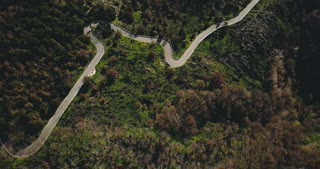 Drone flying over amazing mountain winding road. Aerial top view shot of peaceful forest trees and serpentine roadway 4K
