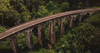 Drone flying over and revealing incredible wide panoramic view of Nine Arch Bridge Ella travel landmark in Sri Lanka.