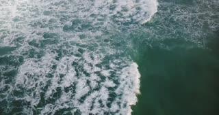 Drone flying over foaming waves breaking in open blue sea, revealing cloudy horizon. Beautiful ocean foam background.