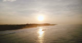 Drone flying right above beautiful sunset ocean. Amazing aerial panorama of setting sun reflection, waves reaching shore