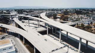 Drone flying right around incredible highway junction interchange in Los Angeles, California, cars moving on many levels