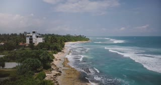 Drone flyover shot of exotic resort beach with little boat, tropical trees, foamy waves crashing over beautiful shore.