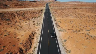 Drone following silver car on empty desert highway road in Arizona, camera tilts up to reveal flat landscape and skyline