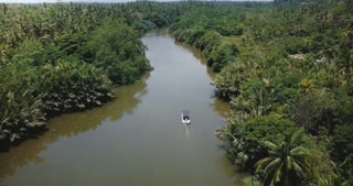 Drone following, tilt down on small white boat sailing along beautiful jungle river in wilderness with sun reflections.