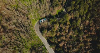 Drone follows blue bus driving along mountain road. Aerial view of a very narrow forest driveway. Travel and tourism. 4K