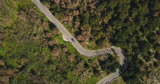 Drone follows car driving along mountain road. Aerial view of a narrow forest driveway. Logistics and transportation. 4K