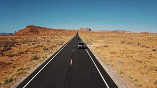 Drone follows two cars driving along beautiful highway road Monuments Valley, wide open endless dry desert landscape.
