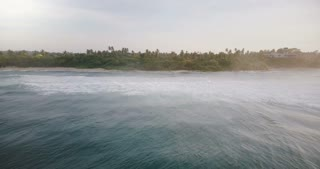 Drone lockdown shot of beautiful calm ocean waves with foam reaching picturesque shore with tropical trees and a house.