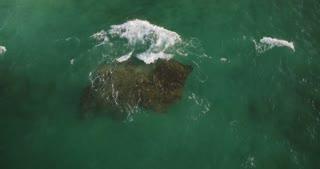 Drone lockdown shot of transparent green waves washing over big stone in beautiful ocean near shore, crashing with foam.