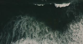 Drone moving right over huge wild dark blue open ocean waves crashing down, white seafoam creating epic natural texture.