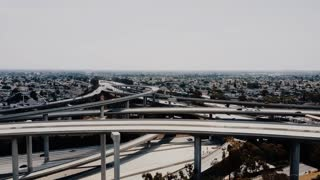 Drone moving to the right over large highway junction in Los Angeles with cars going through multiple roadway levels.