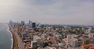 Drone panning right over beautiful coastline, modern buildings of Colombo, Sri Lanka. Aerial view of Asian cityscape.