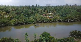 Drone panoramic view of beautiful rainforest river flowing in jungle wilderness with small boat and tropical green trees