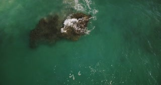 Drone slowly moving over transparent green sea wave crashing over a big cay reef stone, creating beautiful foamy texture