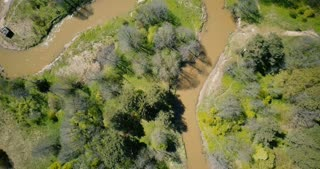 Drone spinning close over winding dirty river. Aerial 4K shot of global environmental responsibility safety problems.