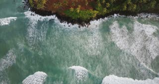 Drone top view lockdown shot of beautiful foaming ocean waves reaching picturesque exotic shore with tropical trees.