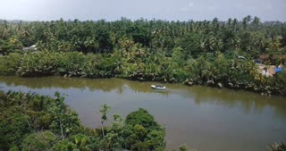 Drone turning left, following small white safari boat sailing along beautiful rainforest river in jungle wilderness.