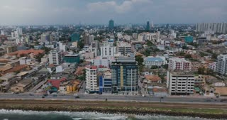 Drone zooming out above Colombo, Sri Lanka panorama. Aerial view of Asian resort town, modern buildings and ocean waves.