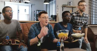 Emotion. African American men watch sports on TV 4K Nerdy mixed race football fans celebrate goal on couch with popcorn.