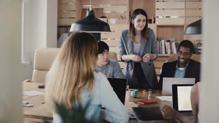 Emotional Caucasian female CEO guides colleagues at multiethnic business team meeting in modern stylish office space 4K.