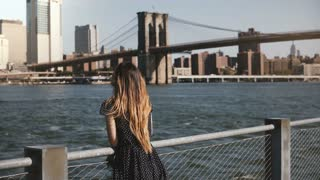Epic panning shot of happy smiling Caucasian woman with flying hair enjoying famous New York City riverside skyline view