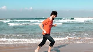 European bearded man running on sea beach. Freedom concept. Male tourist runs barefoot on amazing summer seashore. 4K.